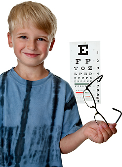 Boy with eyeglasses and vision exam chart